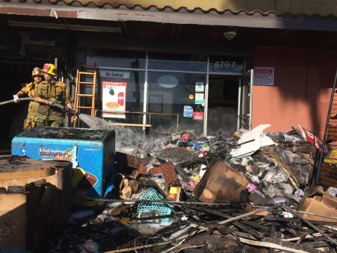 Overhaul pile outside of strip mall unit heavily damaged by fire