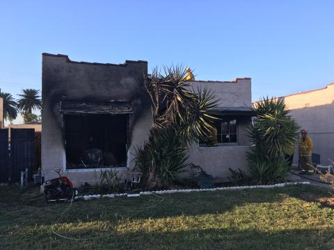Front of small home with visible fire damage