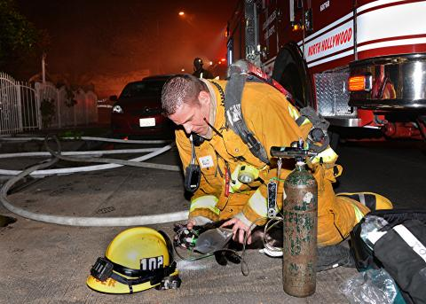 Firefighter using oxygen mask on cat rescued from fire