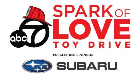 """Spark of Love logo. Graphic has a firefighter helmet on top of abc 7 logo to the left of """"Spark of Love Toy Drive"""" text, with Subaru as presenting sponsor. at the bottom."""