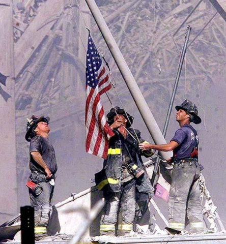 Firefighters raising an American Flag on 9/11 rubble.