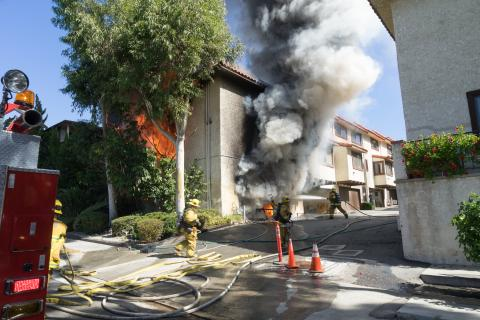 Exterior view of 2 story townhouse with fire showing
