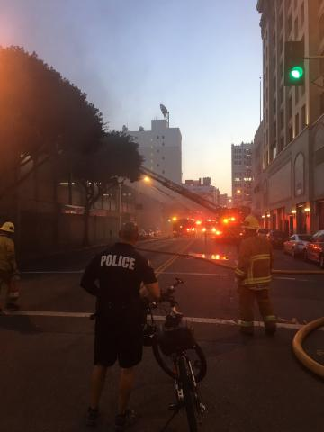 Fire and police seen with building in background, smoke emanating