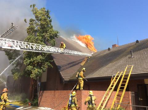 Aerial ladder extends to roof with firefighter on ladder and fire showing through the roof of large church
