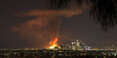 Distant view of Los Angeles skyline with a huge fire and smoke column.