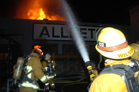 Firefighter with fire hose directing water to roof of building with fire showing