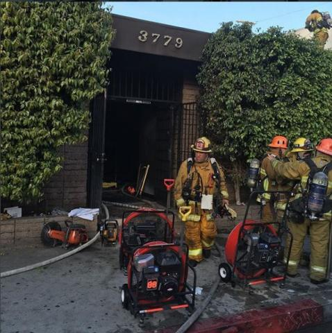 Exterior view of fire building with firefighters and equipment by the door